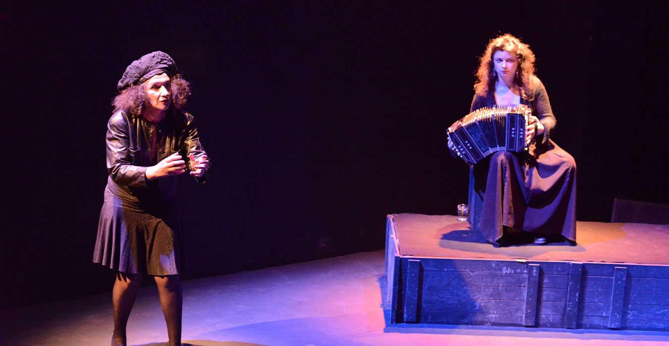 Une femme donne des explications et une accordéoniste en fond