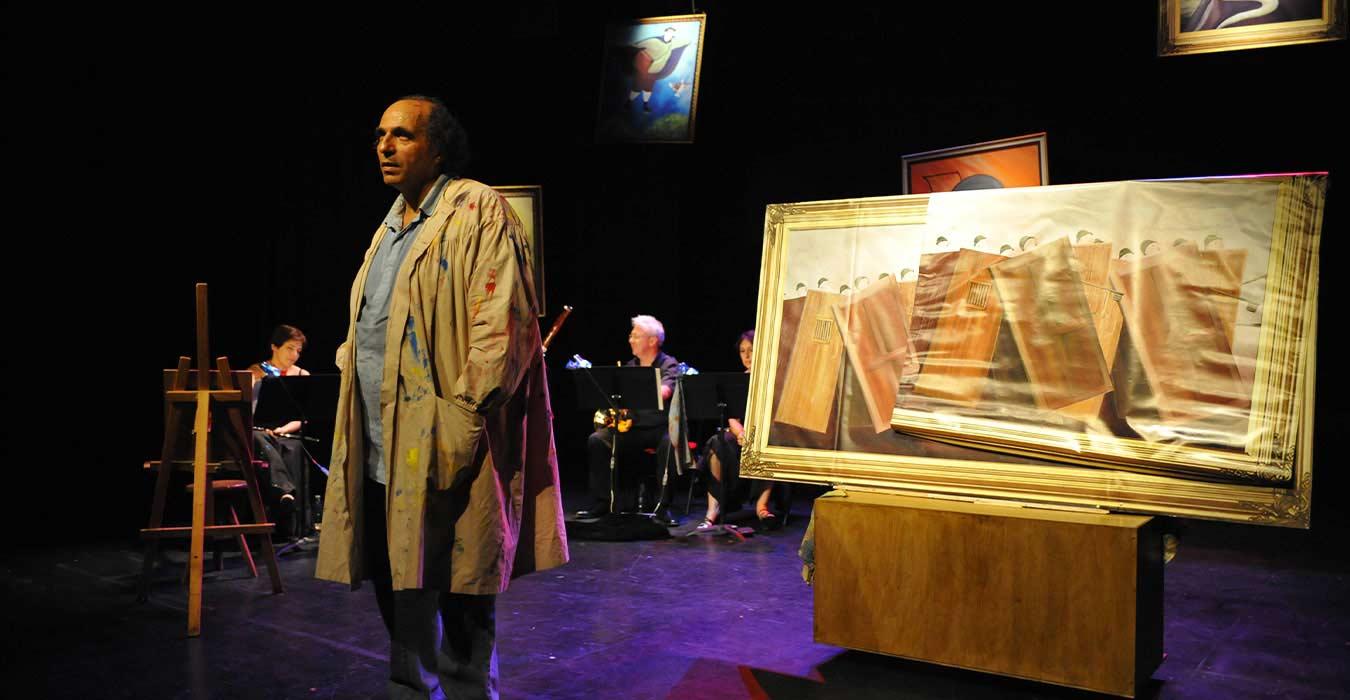 Serge Barbuscia en tenu de peinture avec des musiciens en fond