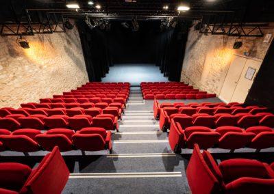 Salle de spectacle depuis le haut des gradins, plateau avec petits pendrillons